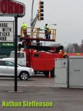 workers putting up sign in wintry mix